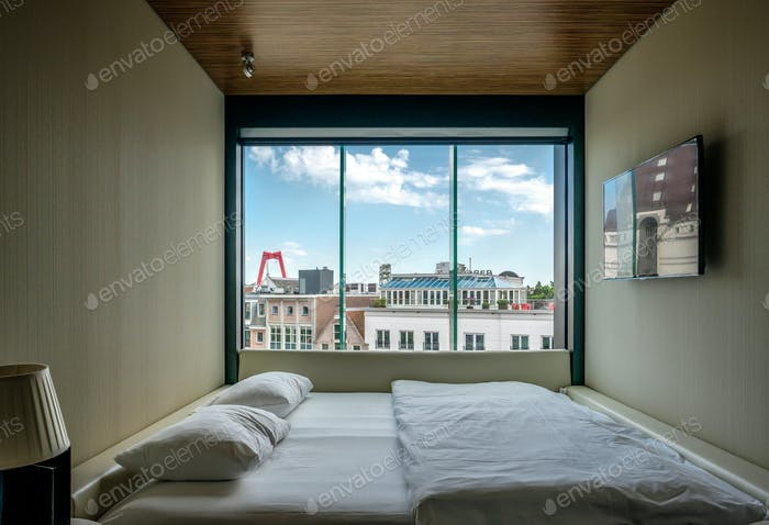 Hotel room with Rotterdam city cityscape skyline with Willemsbrug bridge in window