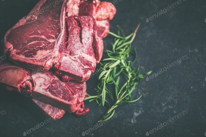 Raw beef meat t-bone steaks with rosemary and spices