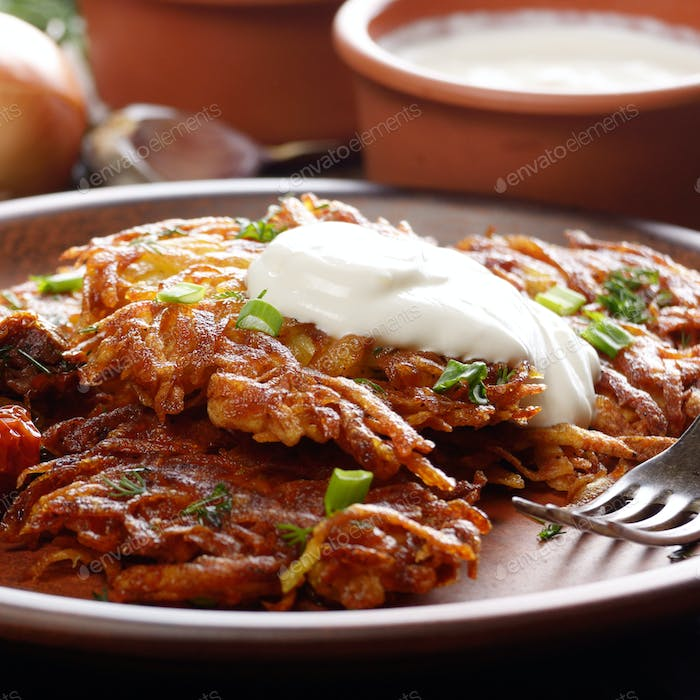 Closeup view at Homemade tasty potato pancakes in clay dish with
