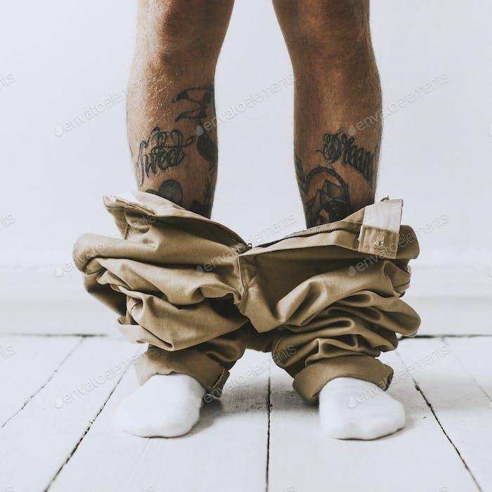Tätowierter Mann erwischt mit heruntergelassenen Hosen