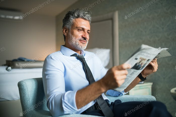 Mature businessman reading newspapers in a hotel room.
