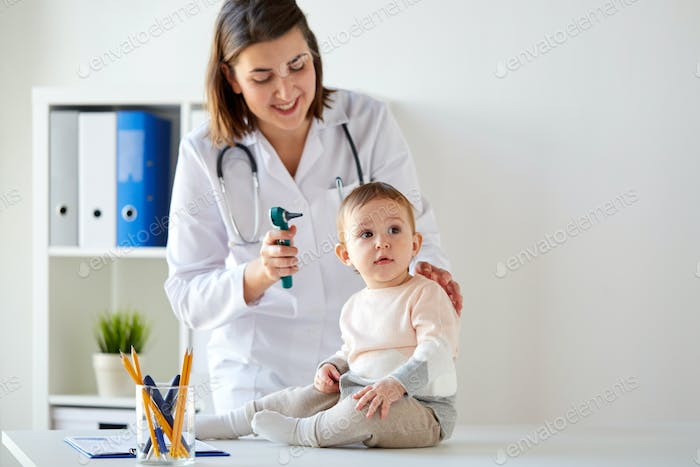 doctor with baby and otoscope at clinic