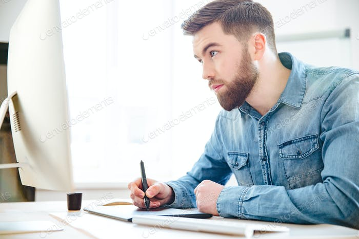 Konzentrierte Designerzeichnung mit Computer und Grafiktablett