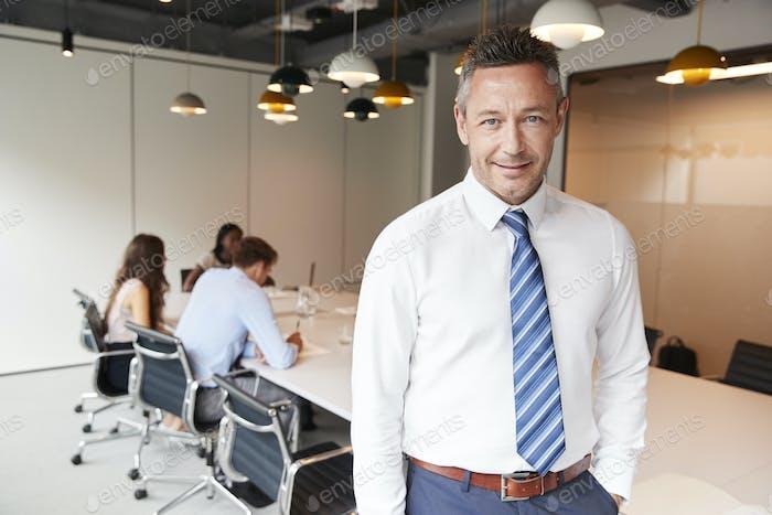 Портрет зрелого бизнесмена, стоящего в современном зале заседаний с коллегами в фоновом режиме