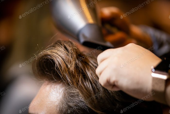 Hands of barber making haircut to young man in barbershop