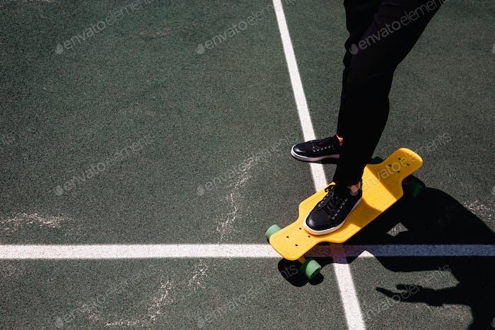 Close up photo of modern man in stylish wear keeping feet on yellow skateboard