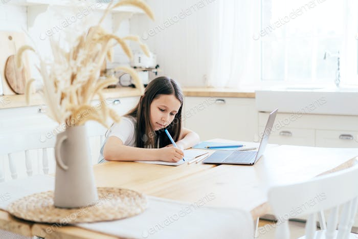 Schoolgirl girl makes homework at the table in front of a laptop. Distance learning