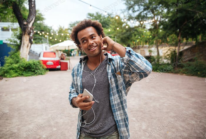 Smiling man in earphones listening to music from cell phone