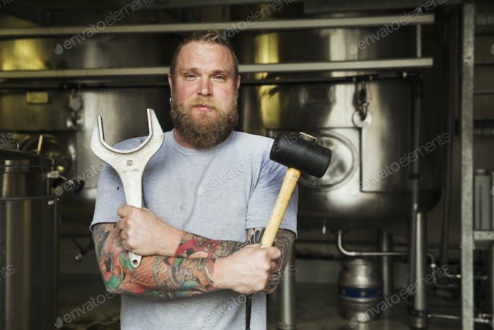 Man standing in a brewery, holding a mallet and a large metal wrench.