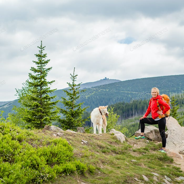 Happy woman hiking walking with dog in mountains, Poland