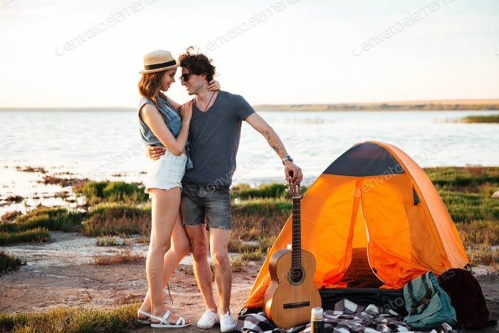 Glückliches Paar in der Liebe umarmt vor einem Zelt