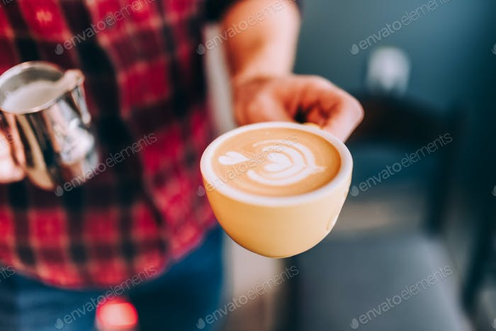 Professional bartender in coffee shop making fresh cappuccino and brewing coffee