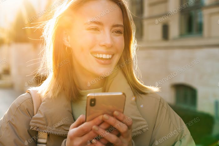Portrait of woman using cellphone and smiling while walking