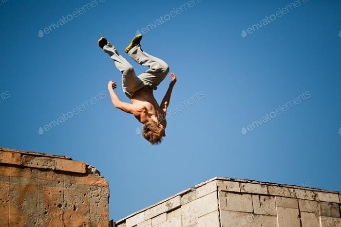 Young man jumping and practicing parkour between two building outside on clear summer day