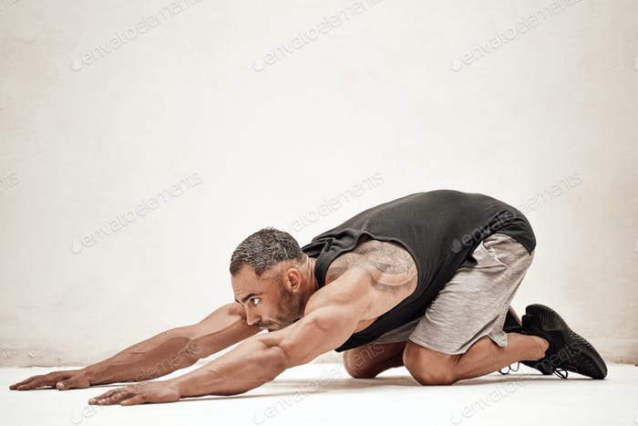 Strong and muscular athlete posing in a bright studio while stretching his muscles