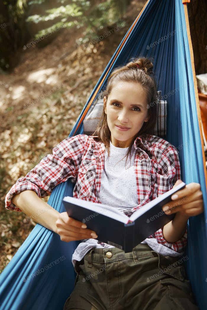 Portrait of woman lying on hammock and reading a book