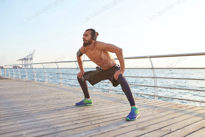 Young masculine sporty bearded guy doing stretching, morning exercises by the sea
