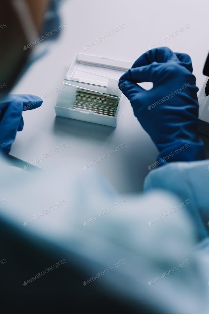 Crop hands putting microscope glasses in box