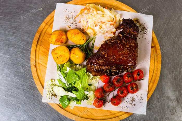 Meat with garnish of vegetables on a wooden board
