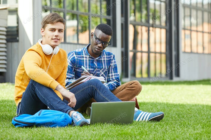 Two Students Sitting on Grass
