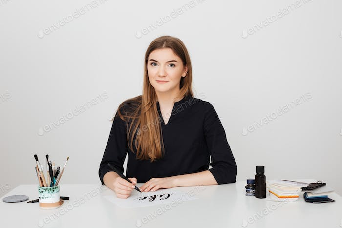 Beautiful photo of young smiling lady sitting at the white desk with pen in hand