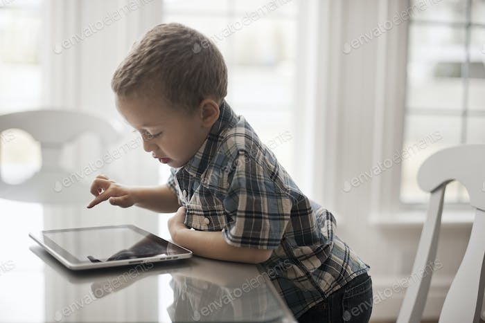 A young child sitting at a table using a digital tablet with a touchscreen.