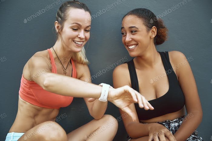 Two laughing friends checking their time after a run together