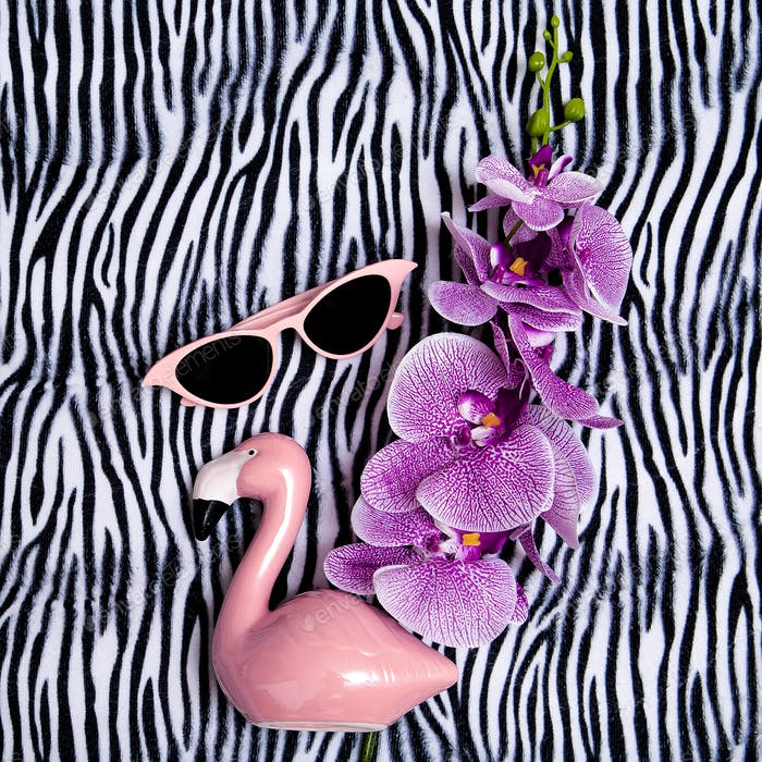 Pink sunglasses and pink flamingo on zebra print background. Minimal beach vibes