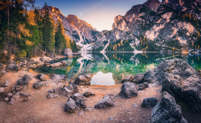 Stones on the coast of Braies lake at sunrise in autumn