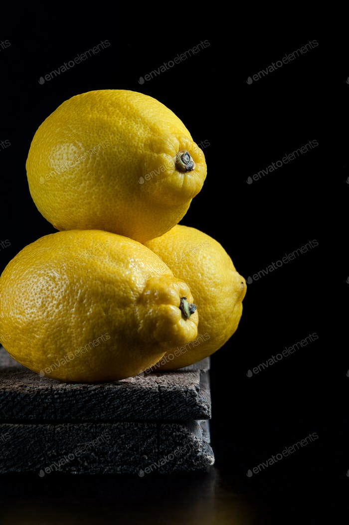 Three ripe lemons on old wooden boards on a black background. Sh