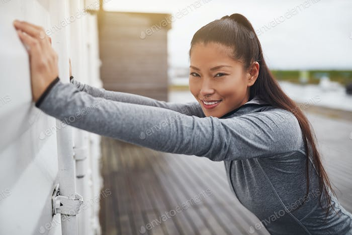 Smiling Asian woman in sportswear stretching outside before exercising
