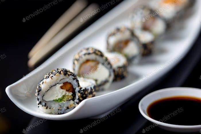 Sushi-Rollen auf weißem Teller. Schwarzer Hintergrund.