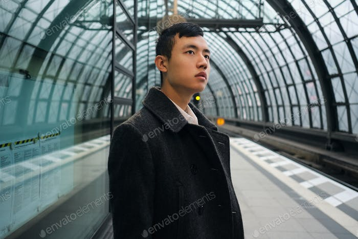 Young Asian businessman in coat thoughtfully looking away waiting train at subway station