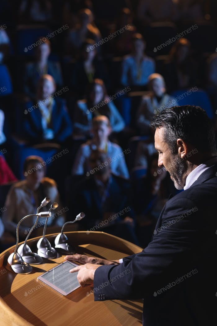 Businessman standing and looking at digital tablet on stage in auditorium