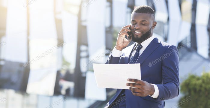 Businessman Negotiating Business Deal By Phone Sitting In Urban Area