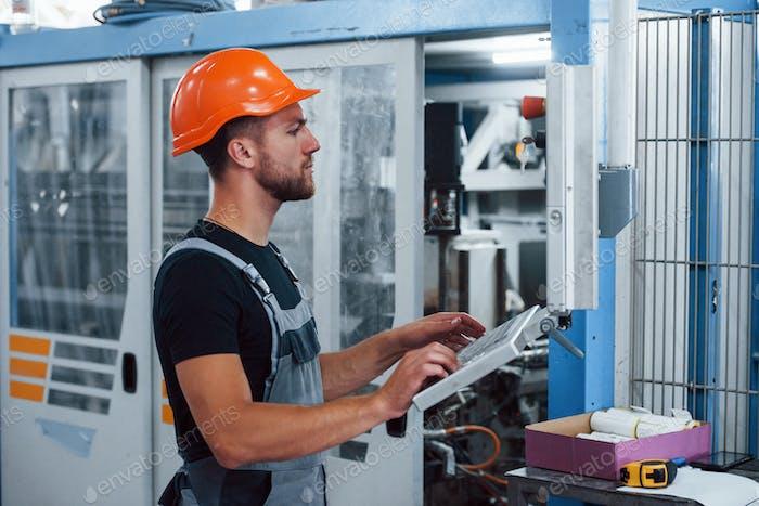 Industriearbeiter in Innenräumen in der Fabrik. Junger Techniker mit orangefarbenem hartem Hut