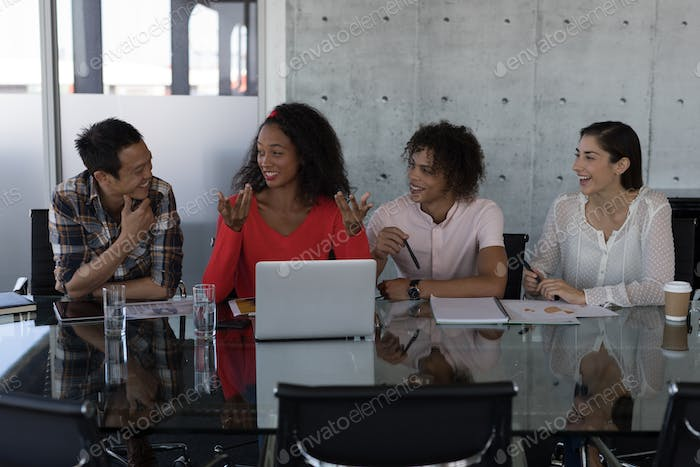 Happy young group of diverse executives talking with each other while sitting at table