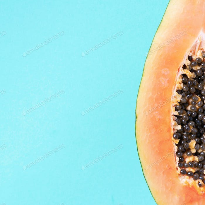 Halved papaya on blue background. Top view. Copy space. Summer time. Tropical travel, exotic fruit