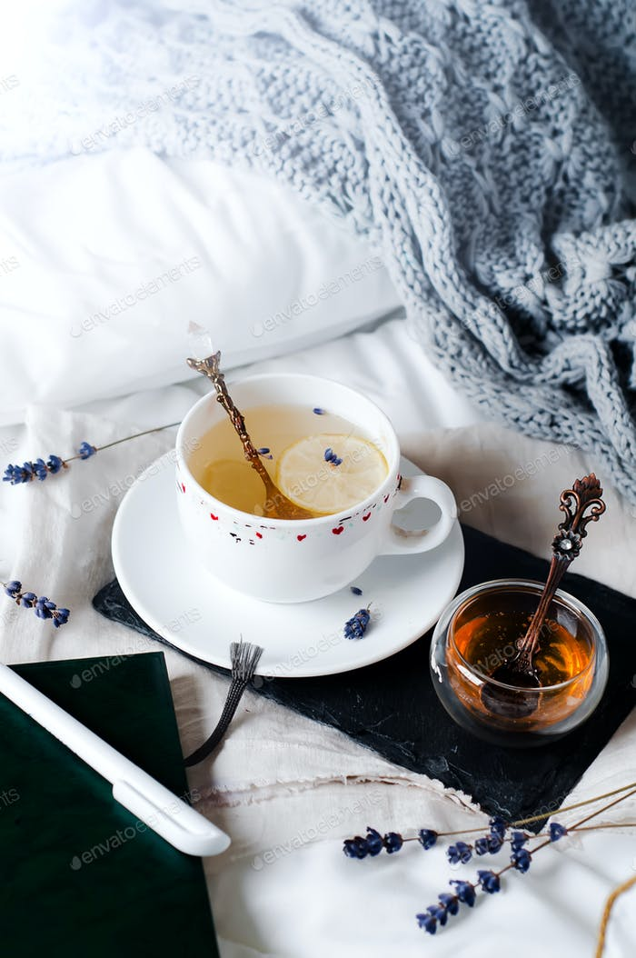 tray with honey and a cup of hot tea in the bed