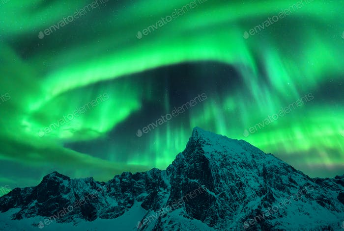 Aurora borealis above the snow covered mountain peak