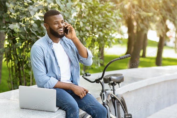 Guy talking on phone, sitting outdoors with laptop and bicycle
