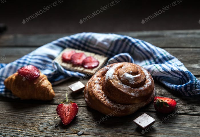 delicious breakfast with strawberries and sweet bun on wooden background. Fruit, food, chocolate