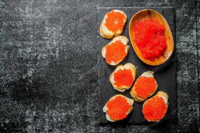 Red caviar in a bowl and caviar sandwiches on a black stone Board.