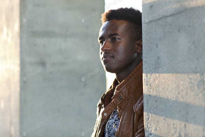 Handsome young black man stands by concrete pillars