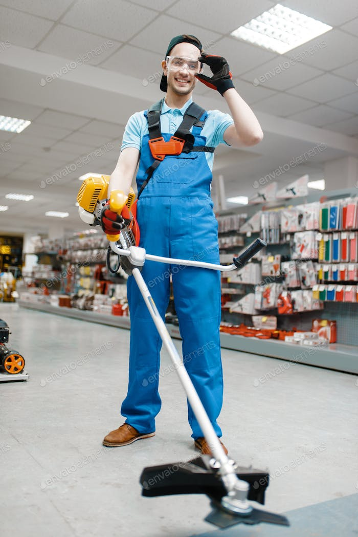 Male worker holds gas trimmer in tool store