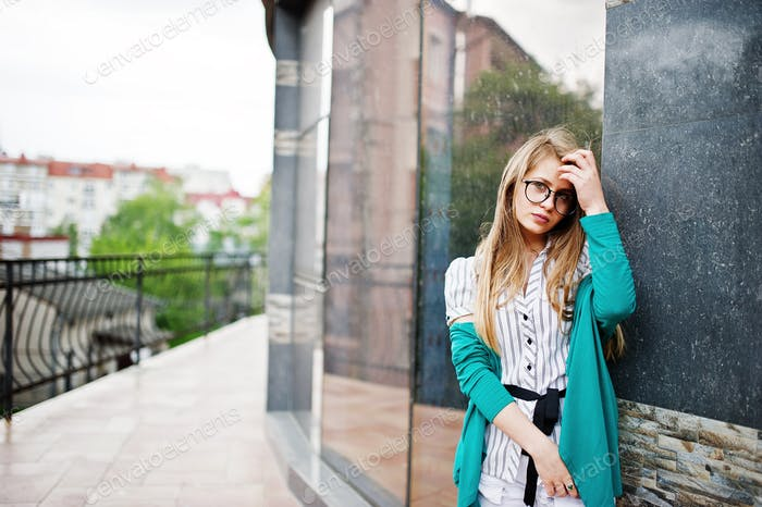 Trendy girl at glasses and ripped jeans against house on street.