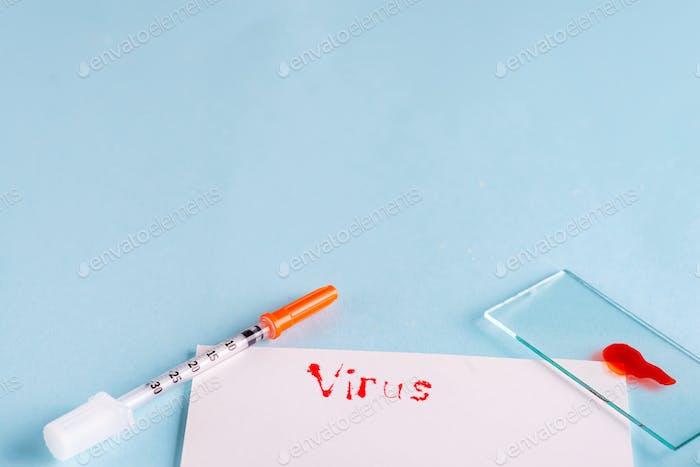 Spritzen Und Reagenzglas mit Blut auf einem blauen Hintergrund mit weißem Papier und der Inschrift Virus