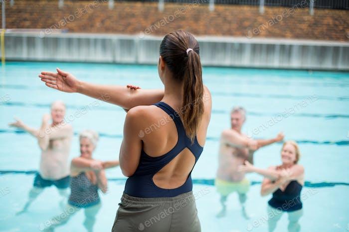 Female yoga trainer instructing senior swimmers