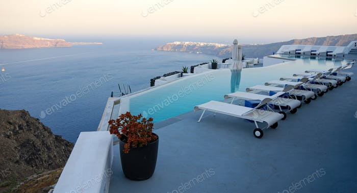 Roof garden of a holiday resort hotel against the ocean at sunset. Oia village, Santorini Island