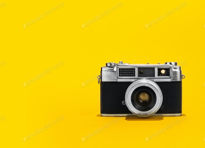 Retro analog film camera on yellow background